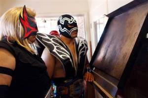 "Mexican wrestlers Renegado and Mr. Tempest look at an image of what they believe is ""Our Lady of Guadalupe"" on a griddle at Las Palmas restaurant in Calexico, Calif."